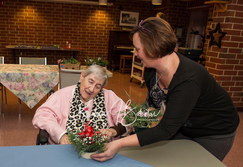 Activities Director Brenda Twardosky helps Mavis Rutherford chose a floral arrangement with a beautiful red bow made by members of the Opechee Garden club and delivered to the Belknap County Nursing Home on Tuesday afternoon.  (Karen Bobotas/for the Laconia Daily Sun)