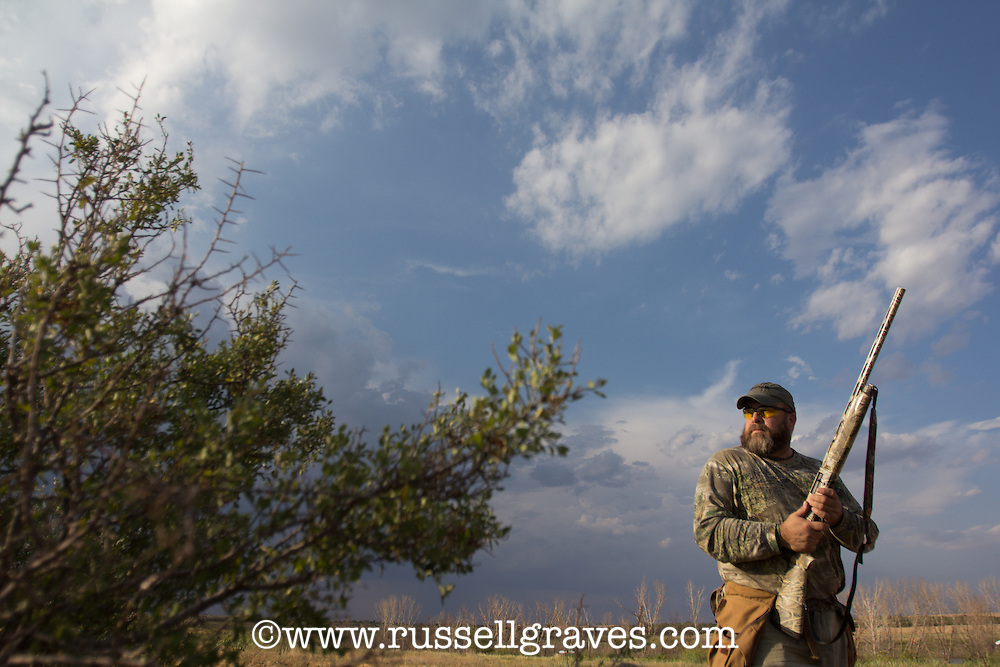 DOVE HUNTER WEARING REALTREE MAX1 CAMO AND HOLDING A BENELLI SHOTGUN