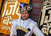 Musician from the Hindu Jea Band of Jaipur waiting for his bus on 4th February 2018 in Jaipur, Rajasthan, India. Established in 1934 this 20-member band band has the distinction of playing at most important events on Rajasthan calendar.