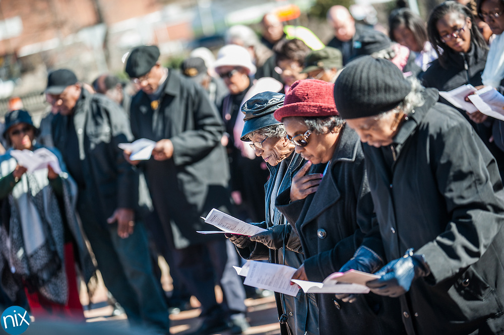 Participants pray during a wreath laying ceremony honoring the legacy of Dr. Martin Luther King Jr. at the MLK Plaza in Concord Monday afternoon.