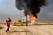 Boots and Coots prepares to attack their first oil well fire in the Rumaila field after a delay of a week due to security, sandstorms, and bureaucracy problems. They are taking a close look shielding themselves with metal roofing pieces that block the intense heat of the fire and working under a water spray. The Rumaila field is one of Iraq's biggest oil fields with five billion barrels in reserve. Many of the wells are 10,000 feet deep and produce huge volumes of oil and gas under tremendous pressure, which makes capping them very difficult and dangerous. Rumaila is also spelled Rumeilah.