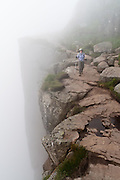 The Pulpit Rock (Preikestolen or Prekestolen) drops precipitously into the fog 604 meters (1982 feet) above Lysefjorden, Norway. The nearest city is Jørpeland, in Strand municipality, Rogaland county, Ryfylke traditional district. Ice Age glaciers deeply gouged a U-shaped valley into a plateau of Precambrian gneiss, carving this cliff high over the North Sea inlet of Lysefjord. Hike 7.6 kilometers (4.8 miles) round trip to one of the most visited natural tourist attractions in Norway. The well marked route requires strong ankles for rock-hopping. For less crowding, start early and hike midweek.