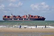 Nederland, Breskens, 5-9-2019Een groot containerschip van rederij UASC is via de Westerschelde op weg naar de haven van Antwerpen . Zeeland, zeeuwse,kust, containervervoer,handel,wereldhandel,sancties,economische, containertransport, consumptie, koopgedrag, consumptiegoederen, .Vlissingen in de achtergrond . Toeristen, badgasten met honden op het strand in de voorgrond.Foto: Flip Franssen