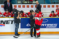 KAMLOOPS, CANADA - NOVEMBER 5:  Sportsnet broadcaster Rob Faulds interviews Riley Sutter #14 of Team WHL on the ice against the Team Russia on November 5, 2018 at Sandman Centre in Kamloops, British Columbia, Canada.  (Photo by Marissa Baecker/Shoot the Breeze)