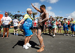 A Gold Coast 2018 volunteer dances with an Aboriginal elder and performers during the Welcome ceremony at The Athletes Village for the 2018 Commonwealth Games, Gold Coast, Australia.