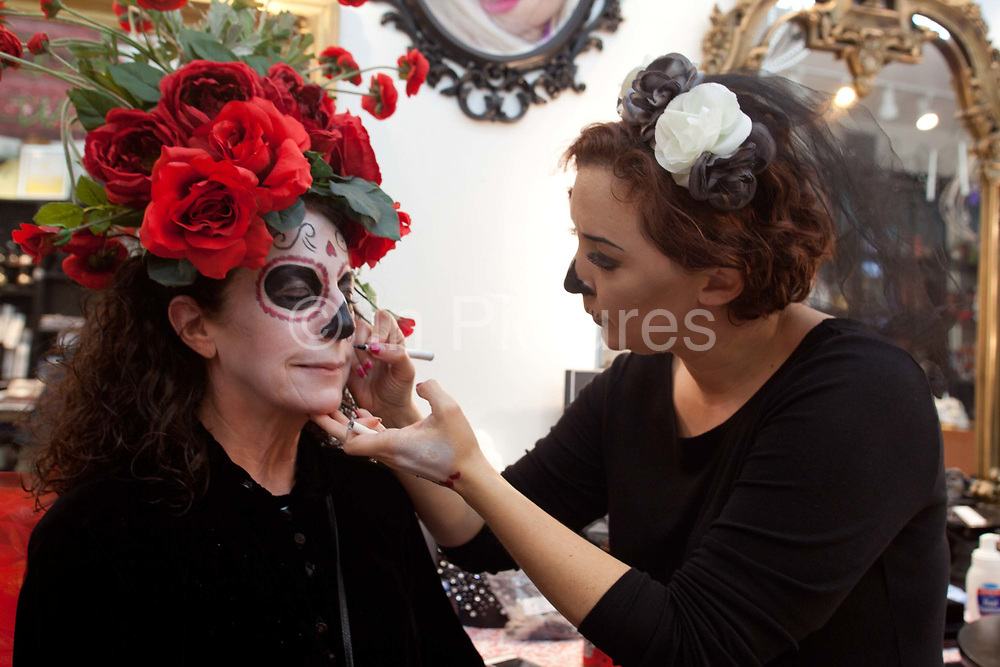 People having their makeup done in a specialist makeup bar: Voodoo Makeup, set up by Aimee Carr and Ron Carr, it provides makeup that is gluten free, corn free, soy free makeup that is 100% organic, vegan, and chemical free. French Quarter, New Orleans, Louisiana, USA. walking down the street in the French Quarter,
