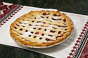 Homemade cherry pie on table runner.