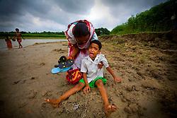 Aging sex worker Josna, 60, consoles  her crying daughter Tanya, 7 in Faridpur, Bangladesh.