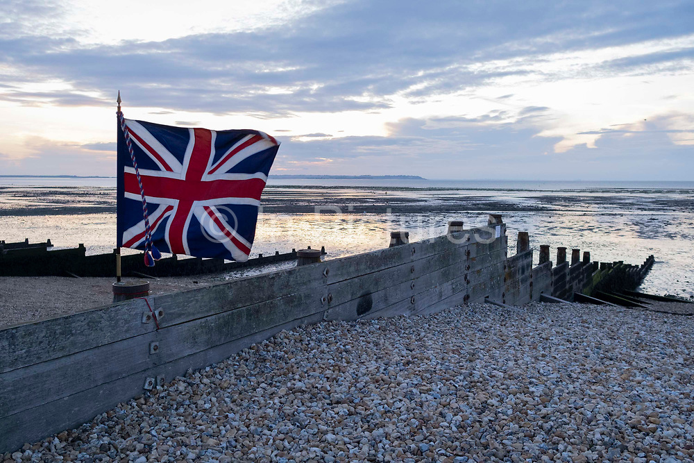 A Union Jack flag flutters in a soft breeze  over a low-tide evening beach sunset, on 27th July 2021, in Whitstable, Kent, England.