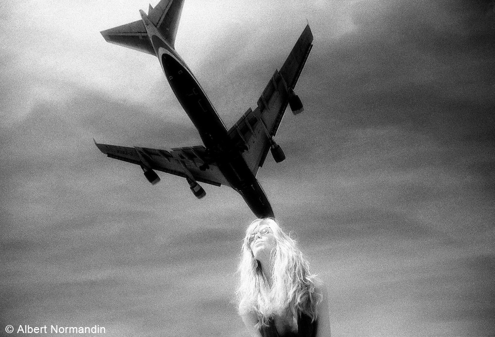 Woman with hair blowing in face and airplane above