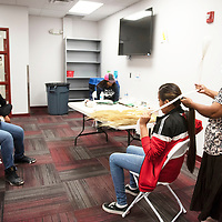 Tristah Loley sits while Vanessa Begay ties a traditional Navajo hair bun during the breakout session Diné Tsiiyéé (Hair Bun) is Power led by Begay at the Eastern Navajo Nation Youth Summit, Wednesday, June 19 at Navajo Technical University in Crownpoint.