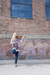 Caucasian teenage girl playing violin in front of brick wall, Munich, Bavaria, Germany