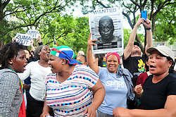 JOHANNESBURG, SOUTH AFRICA – APRIL 07: Protestors outside the Gupta's Saxonwold residence call for President Zuma to step down, the Guptas through their businesses are accused of links to goverment officials and the president, in Johannesburg, South Africa, 07 April 2017. Businesses closed and South Africans from numerous political, religious, labour and civic groups gathered at central points across the entire country protesting against President Zuma's recent government reshuffle appointing 10 new ministers and 10 new deputy ministers including the axing of the finance minister. Photo: Dino Lloyd