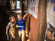 06 MARCH 2014 - MAE SOT, TAK, THAILAND: Students in the hallway at the Sky Blue School. There are approximately 140 students in the Sky Blue School, north of Mae Sot. The school is next to the main landfill for Mae Sot and serves the children of the people who work in the landfill. The school relies on grants and donations from Non Governmental Organizations (NGOs). Reforms in Myanmar have alllowed NGOs to operate in Myanmar, as a result many NGOs are shifting resources to operations in Myanmar, leaving Burmese migrants and refugees in Thailand vulnerable. The Sky Blue School was not able to pay its teachers for three months during the current school year because money promised by a NGO wasn't delivered when the NGO started to support schools in Burma. The school got an emergency grant from the Burma Migrant Teachers' Association and has since been able to pay the teachers.      PHOTO BY JACK KURTZ