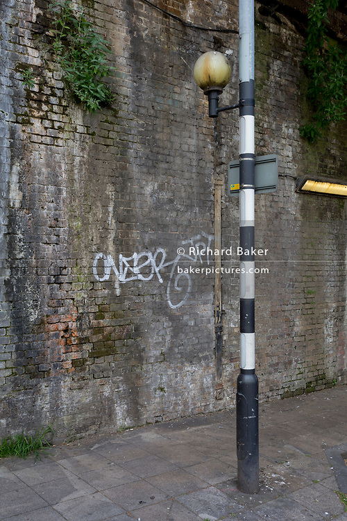 An old belisha beacon and small Mini Cab business landscape at a crossing beneath one of the many Victorian bridges near Waterloo mainline station, on 2nd May 2019, in London, England.