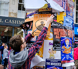 Edinburgh Scotland 7th August 2016 :: Performers from Fringe shows entertain in the High Street to promote their shows.<br /> <br /> A performer placing a poster for his show on a pillar in the High Street<br /> <br /> (c) Andrew Wilson   Edinburgh Elite media
