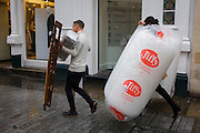 Shop workers carry retail items in a central London street.
