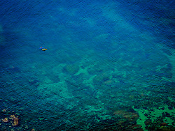 Aerial view of people kayaking on clear blue water of Bay of Plentzia