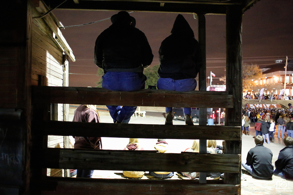 Phillip and Stephanie Weitner, right, sit on a fence as thousands of Texas A&M Aggie fans fill Stockyards Station before the pre-Cotton Bowl midnight Aggie Yell practice in Fort Worth, Texas, on January 4, 2012.  (Stan Olszewski/The Dallas Morning News)