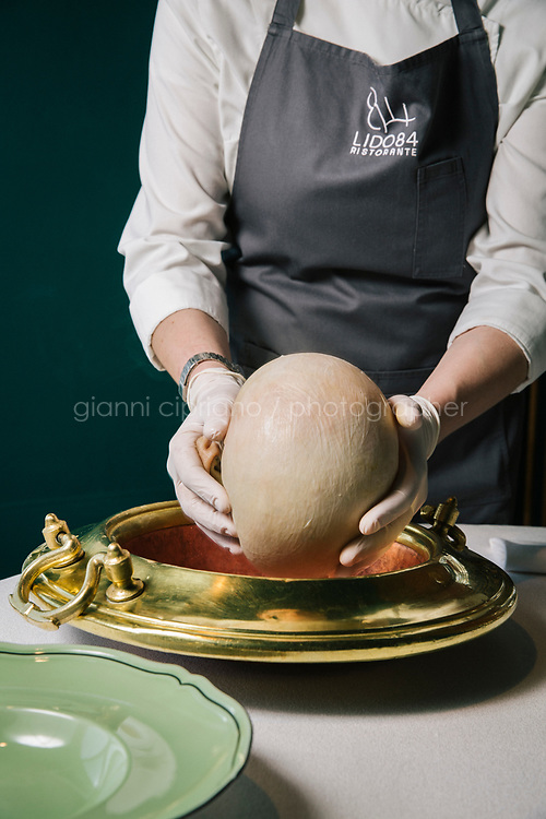 """GARDONE RIVIERA, ITALY - 20 APRIL 2018: A waiter shakes a pig's bladder containing a """"cacio e pepe"""" before cutting it and serving the pasta at Lido 84 restaurant in Gardone Riviera, Italy, on April 20th 2018.<br /> <br /> Lake Garda is the largest lake in Italy. It is a popular holiday location located in northern Italy, about halfway between Brescia and Verona, and between Venice and Milan on the edge of the Dolomites. The lake and its shoreline are divided between the provinces of Verona (to the south-east), Brescia (south-west), and Trentino (north)."""