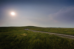 Late afternoon sunlight bathes the rolling hills of the nearly 11,000 acre Tallgrass Prairie National Preserve in the Flint Hills of Kansas in Chase County near the towns of Strong City and Cottonwood Falls. Pictured is the main road as it travels through the Windmill Pasture. Less than four percent of the original 140 million acres of tallgrass prairie remains in North America. Most of the remaining tallgrass prairie is in the Flint Hills in Kansas. Tallgrass Prairie National Preserve is the only unit of the National Park Service dedicated to the preservation of the tallgrass prairie ecosystem. The Tallgrass Prairie National Preserve is co-managed with The Nature Conservancy.