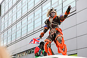 Hackney carnival 2014. The procession started in Ridley Road and passed by the The Hackney Town Hall with thousands of spectators lining the road. A man dressed up as tiger creature does his moves on top of a passing van.