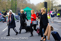Women attending a conference on Park Lane have to walk to the venue as all traffic is denied access as hundreds of environmental protesters from Extinction Rebellion occupy Marble Arch, camping in the square and even on the streets, blocking access to traffic on Park Lane and Oxford Street in London's usually traffic-heavy west end. . London, April 16 2019.