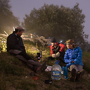 The expedition team cooks dinner at dusk near the summit of Santa María Volcano.