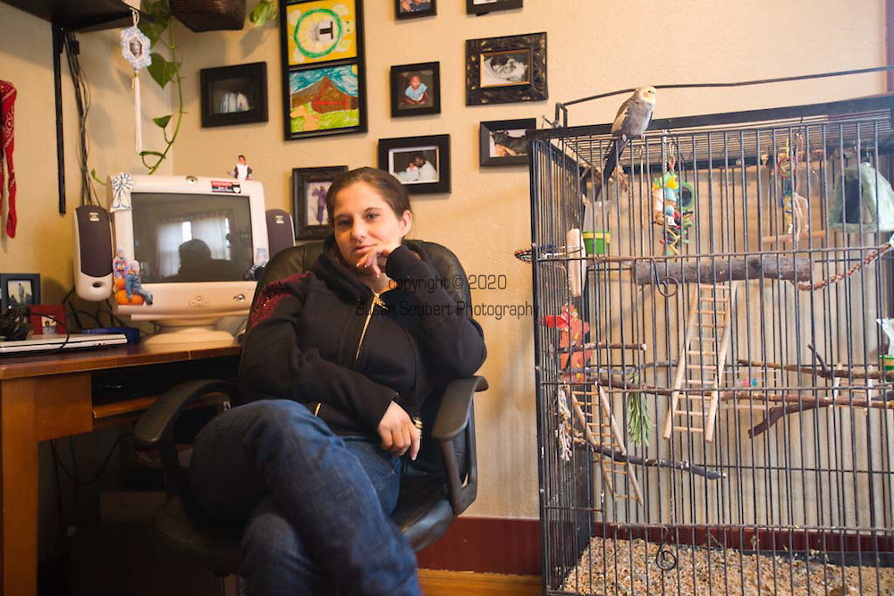"""Margaret B. Jones in her office in her home in Eugene, Oregon.  Her bird, """"Chuck"""" is sitting on the cage next to her."""