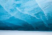 An undercut roof of glacier ice over freshly fallen snow on Rabotbreen, Svalbard.