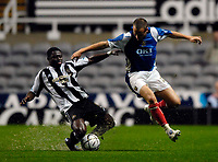 Photo: Jed Wee.<br /> Newcastle United v Portsmouth. Carling Cup. 25/10/2006.<br /> <br /> Newcastle's Obafemi Martins (L) slides in to dispossess Portsmouth's Matthew Taylor.