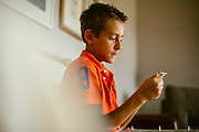 Boy looks through photo album. Country lifestyle documentary portraits. <br />