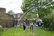 Young people play on the swings in the rotunda gardens in Cressingham Gardens on 30th May 2015 in South London, United Kingdom. Cressingham Gardens is a council garden estate, located on the southern edge of Brockwell Park. It comprises of 306 dwellings and built to the design of Lambeth Borough Council architect Edward Hollamby in the early 1970s. In 2012, Lambeth Council proposed regeneration of the estate, a decision highly opposed by many residents. Since the announcement, the highly motivated campaign group Save Cressingham Gardens has been active.