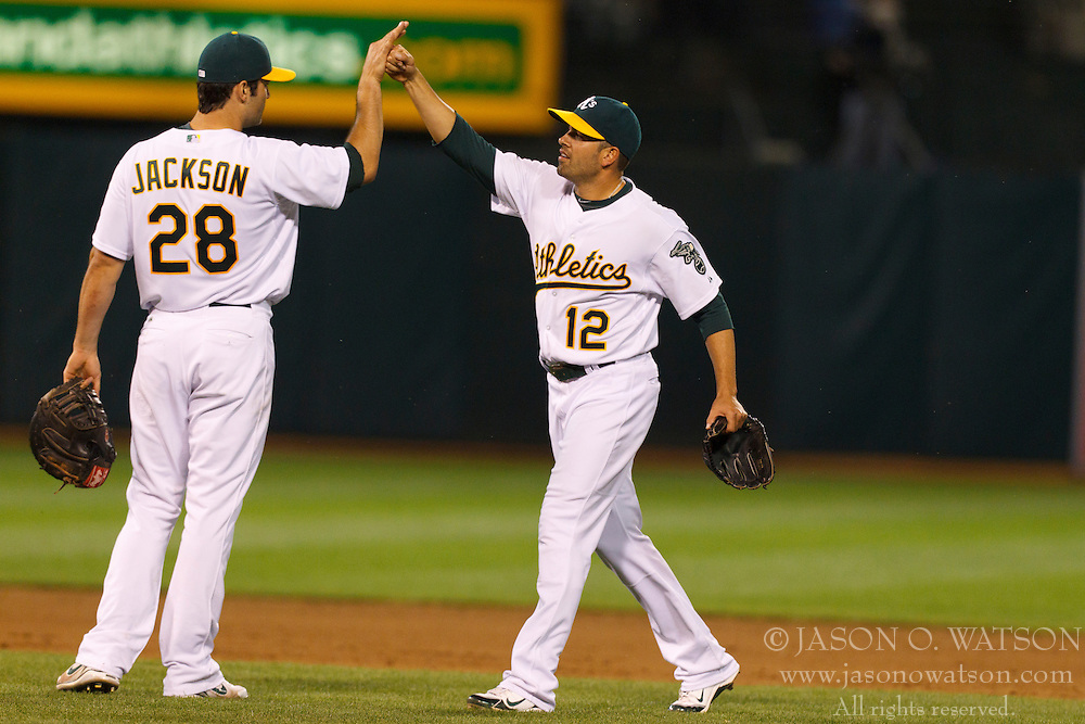 May 4, 2011; Oakland, CA, USA;  Oakland Athletics right fielder David DeJesus (12) celebrates with right fielder Conor Jackson (28) at the end of the game against the Cleveland Indians at Oakland-Alameda County Coliseum. Oakland defeated Cleveland 3-1.