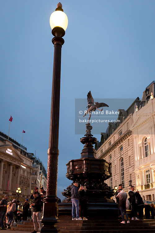 "The Eros statue and lamp post at Piccadilly Circus, on 22nd November 2019, in Westminster, London, England. Eros aka 'The Shaftesbury Memorial Fountain' is located at the southeastern side of Piccadilly Circus in London, United Kingdom. Moved after World War II from its original position in the centre, it was erected in 1892–1893 to commemorate the philanthropic works of Lord Shaftesbury, who was a famous Victorian politician and philanthropist. The monument is surmounted by Alfred Gilbert's winged nude statue generally, though mistakenly, known as Eros. This has been called ""London's most famous work of sculpture."""