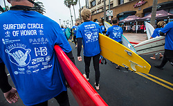 June 20, 2017 - Huntington Beach, California, USA - All of the nearly 600 surfers wore special shirts as they make their way along Main Street in downtown Huntington Beach as the procession heads to the ocean to create the world's largest paddle out ''Circle of Honor'' in Huntington Beach Tuesday morning, June  20, 2017. (Photo by Mark Rightmire, Orange County Register/SCNG) (Credit Image: © Mark Rightmire, Mark Rightmire/The Orange County Register via ZUMA Wire)