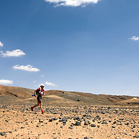 26 March 2007:  A participant runs across a very rocky plain during the second stage (21.7 miles) of the 22nd Marathon des Sables between Khermou and jebel El Otfal. The Marathon des Sables is a 6 days and 151 miles endurance race with food self sufficiency across the Sahara Desert in Morocco. Each participant must carry his, or her, own backpack containing food, sleeping gear and other material.