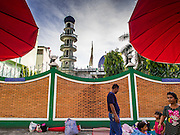 27 JULY 2014 - HAT YAI, SONGKHLA, THAILAND: Thai Buddhists set up their stand selling durian fruit in front of the Pakistan Mosque (Masjid) in Hat Yai, Thailand. Hat Yai is the 4th largest city in Thailand and the largest outside of the Bangkok metropolitan area. It's less the 50 miles from the Malaysian border and is a popular vacation spot for Malaysian and Singaporean tourists.     PHOTO BY JACK KURTZ