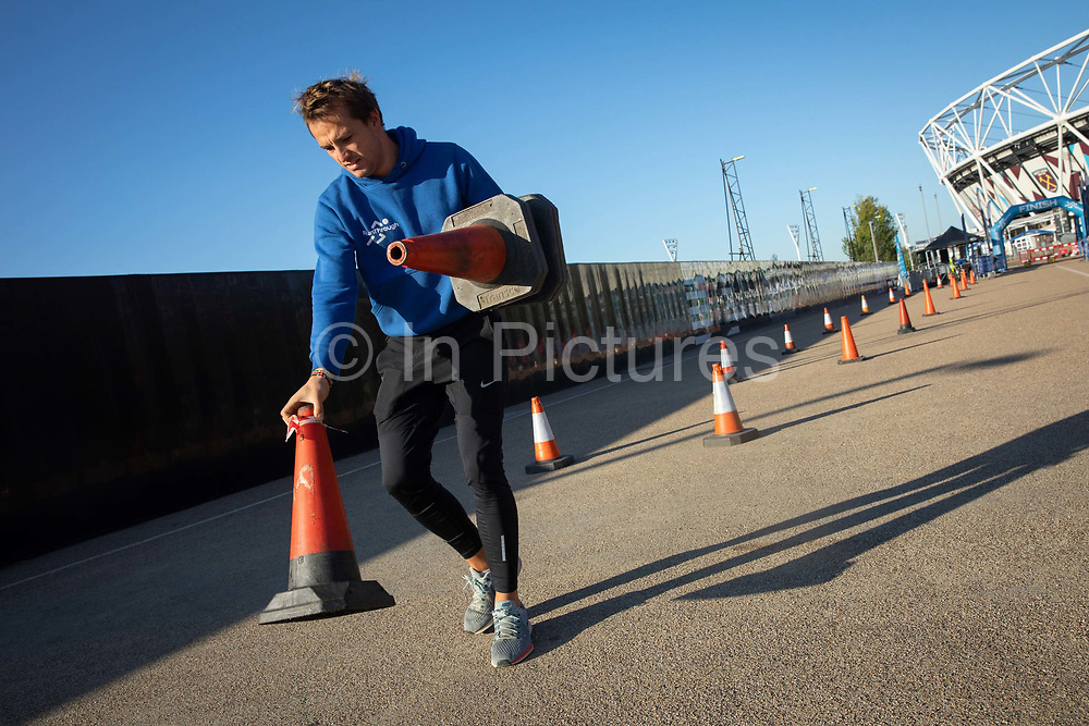 A steward sets up course markers ahead of a 10 kilometre running event at the Queen Elizabeth Olympic Park on the 21st September 2019 in London in the United Kingdom. RunThrough is a London based running community who organise regular running events, training sessions as well as coaching.