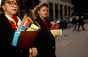 Women office workers dash through a City of London street, the heart of the capital's financial district. Carrying an armful of paper files and folders, clasped in their arms that make their way across the city en route to a meeting with associates. Their education and careers have taken them to positions of influence and success, still hard to do in 90s Britain.
