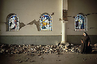 April 1982, Popayan, Colombia --- On Easter, a nun surveys the damage to the interior of a church caused by an earthquake. Popayan, Columbia, April 1982. --- Image by © Owen Franken/CORBIS