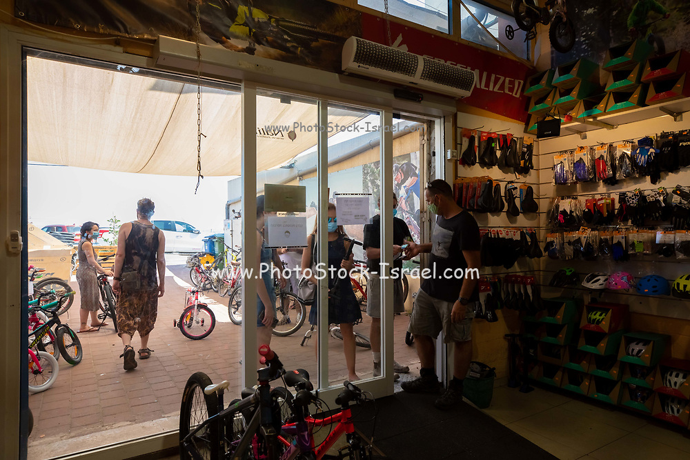 Bicycle shop during the COVID-19 Pandemic. Customers wait outside the small store for service and are served at the door. Customers are obliged to wear facial masks at all times while the employees of the shop seem to think that they are exempt. This clearly violates the regulations, endangers the public and erodes trust