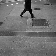 A pedestrian walks past grates which serve as the exhaust vents for heating the skyscrapers on at the corner of York Street and Wellington Avenue West located in Toronto's Financial District..(Credit Image: © Louie Palu/ZUMA Press)