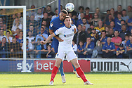 AFC Wimbledon defender Rod McDonald (26) battles for possession with Portsmouth attacker Oliver Hawkins (9) during the EFL Sky Bet League 1 match between AFC Wimbledon and Portsmouth at the Cherry Red Records Stadium, Kingston, England on 13 October 2018.