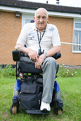 Male wheelchair user outside his house,