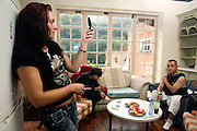 Daniela, 26, from Romania, (left) is snapping a few pictures with her camera-phone inside the kitchen of the Ingram Avenue mansion on Saturday, June 16, 2007, in Hampstead, London, England. Nego, 31, (right) her Romanian partner is looking at her while Lulu, 33, another Romanian squatter (centre) is eating some food on the back. The 22-room mansion was last sold for UK£ 3.9M in 2002 and is now awaiting planning permissions to be demolished. Two new houses will soon be taking its place. Million Dollar Squatters is a documentary project in the lives of a peculiar group of squatters residing in three multi-million mansions in one of the classiest residential neighbourhoods of London, Hampstead Garden. The squatters' enthusiasm, their constant efforts to look after what has become their home, their ingenuity and adventurous spirit have all inspired me throughout the days and nights spent at their side. Between the fantasy world of exclusive Britain and the reality of squatting in London, I have been a witness to their unique story. While more than 100.000 properties in London still lay empty to this day, squatting provides a valid, and lawful alternative to paying Europe's most expensive rent prices, as well as offering the challenge of an adventurous lifestyle in the capital.