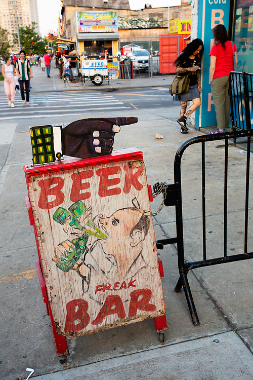 A sidewalk sign outside the Freak Bar of Surf avenue, both a bar and an entrance to the Coney Island Museum .