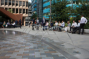 City workers take a break at lunchtime in the now redeveloped area with modern glass offices, angular structures and creative fountains at Aldgate in the City of London, England, United Kingdom. As Londons financial district grows in height, the architecture has changed the face of Londons financial district.