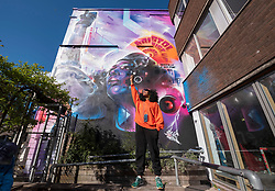 "© Licensed to London News Pictures; 02/04/2021; Bristol, UK. JEN REID gives her Black Lives Matter salute in front of ""United Souls United Goals"", an artwork by artist Mr Cenz, of a giant mural of Jen Reid, the woman who stood on the plinth of the statue of Edward Colston after it was torn down at a Black Lives Matter protest in Bristol in 2020 and of whom a statue was made and temporarily placed on the plinth. The mural is on the wall by The Canteen on Stokes Croft directly opposite Banksy's Mild Mild West mural, and replaces an earlier mural of Breakdancing Jesus. The mural is launched by The Bristol Eighteen and has the welcoming message ""Rise up Bristol, stand tall... Bristol's a city for all"" by poet Lawrence Hoo with Bristol's own street artist Inkie lending a hand to convey Lawrence Hoo's open-arms message of togetherness. The piece has been created to commemorate the Black Lives Matter protest in Bristol on June 7th 2020 and promote the ongoing global anti-racism movement. The Bristol Eighteen was formed, in the wake of the removal of Edward Colston's statue, to create a vehicle to raise funds for anti-racist educational organisations. Photo credit: Simon Chapman/LNP."