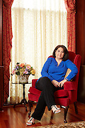 Portrait of lady in a red chair.<br />